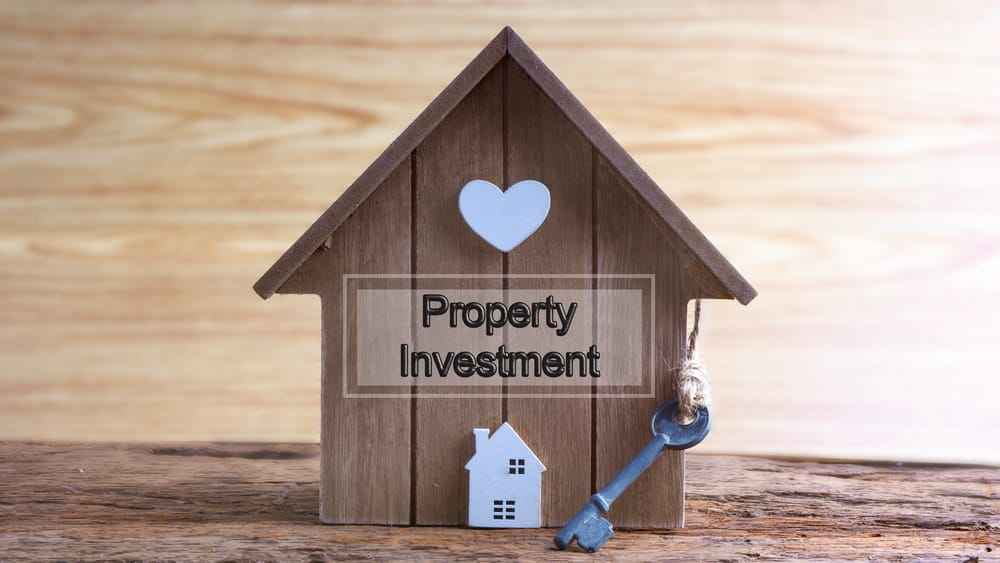 Wooden house with investment sign
